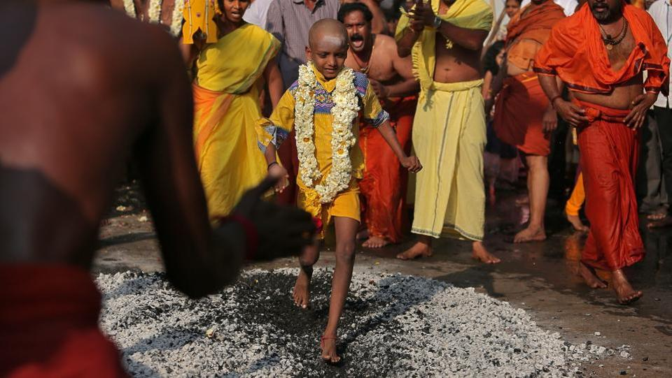 A boy walks over burning coal as part of the Thaipusam festival in Chennai on January 31, 2018. Hindu devotees across Malaysia, Singapore, India, Sri Lanka celebrated the annual Thaipusam festival, with many piercing their skin with hooks and skewers to show devotion to the deity Murugan. (P. Ravikumar / REUTERS)