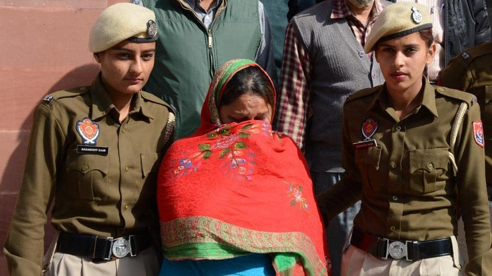 Accused Sweety being taken away after the recovery of gold and opium from her locker at the State Bank of India branch in SA Jain College in Ambala on Friday.