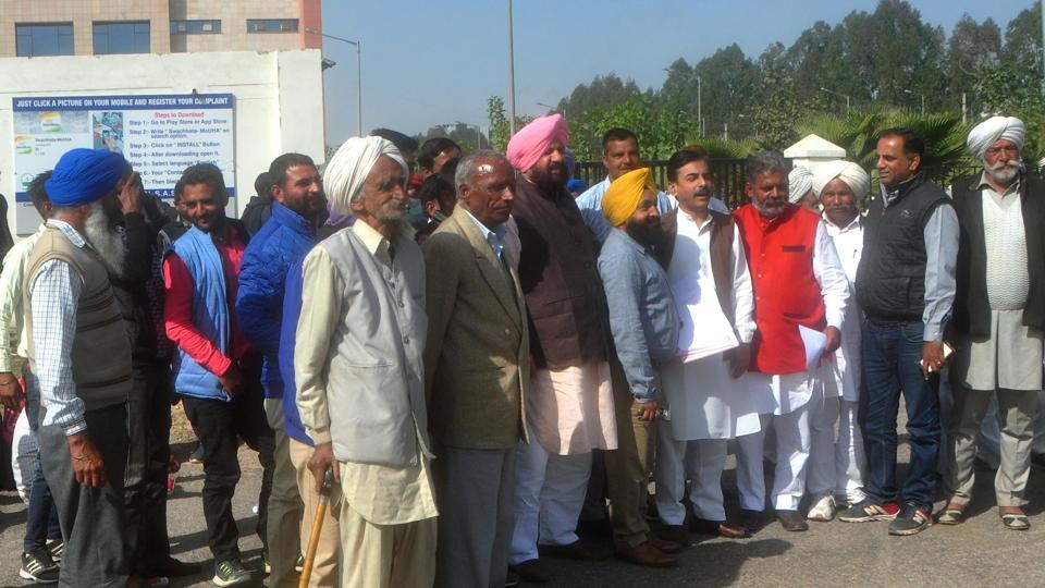 BJP state unit vice-president Harjit Grewal (3L) and secretary Vineet Joshi (5L) with villagers protesting against the 'improper' notification, at the DC office in Mohali on Friday.