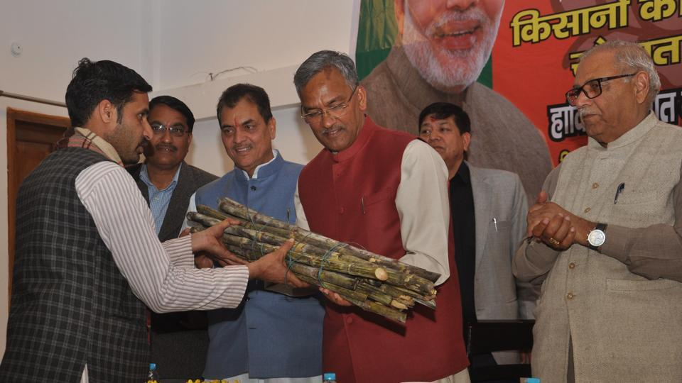 Chief minister Trivendra Singh Rawat  accepts sugarcane from a farmer at a convention in Dehradun.