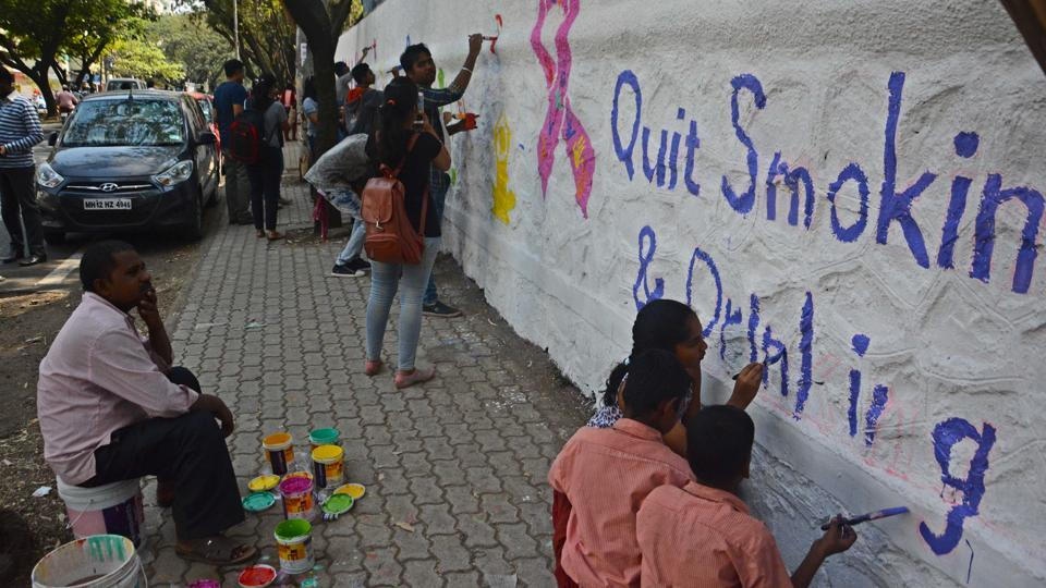 Puneites paint city walls along with Indus Health Plus to create awareness about cancer in Pune on Saturday.