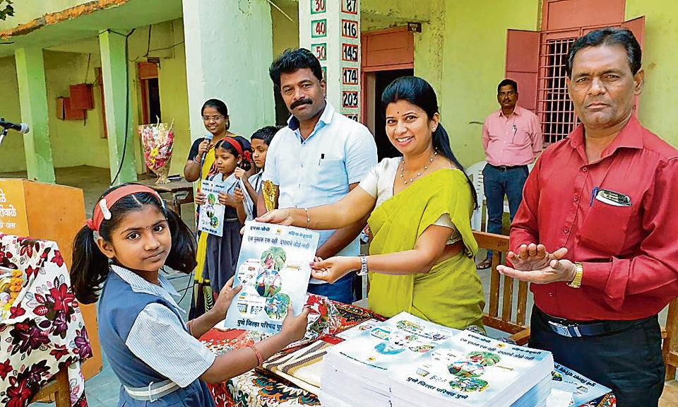 Representatives from the zilla parishad distributing the book based on a monthly syllabus to students.