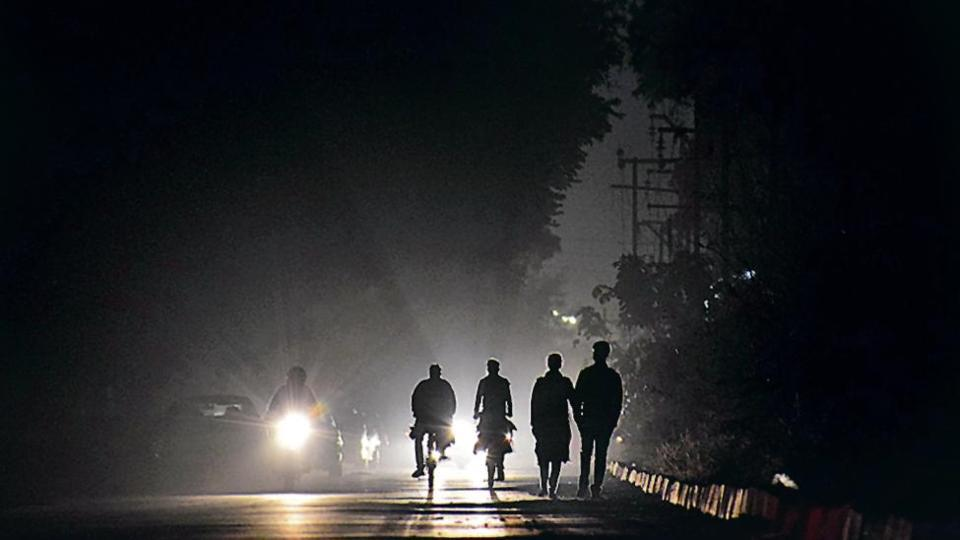 Commuters moving in pitch dark in the absence of functional streetlights at a service lane in Sector 43 in Chandigarh.