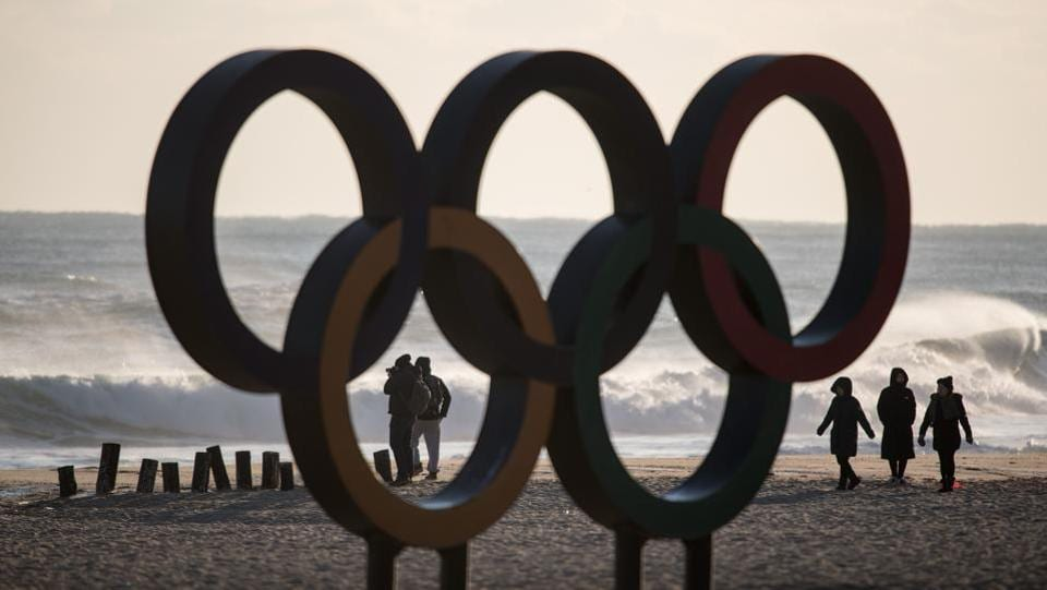 People walk before the Olympic Rings during sunrise on Gyeongpo beach in Gangneung, the host city of the ice venues for the Winter Olympic Games. (Ed Jones / AFP)
