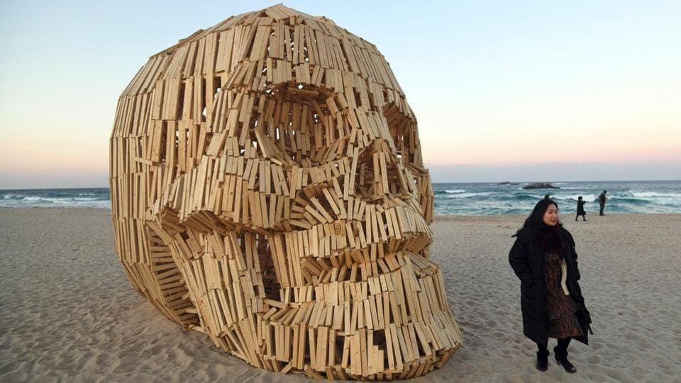 A woman walks past an art work installation of a large wooden skull at Gyeongpo beach. (Jung Yeon-Je / AFP)