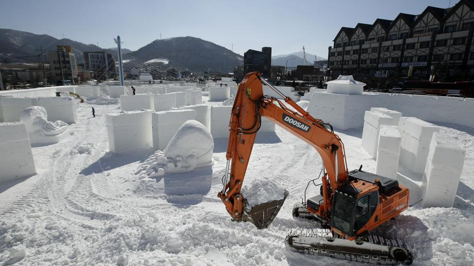 Workers toil on a large ice sculpture at the Pyeongchang Olympic Plaza as preparations continue ahead of the big day. (Charlie Riedel / AP)