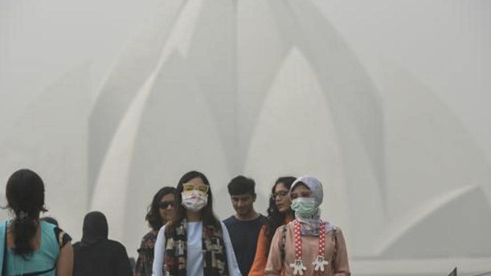 Tourists wearing masks as they visit Lotus Temple on a smoggy morning in New Delhi on November 7, 2017.