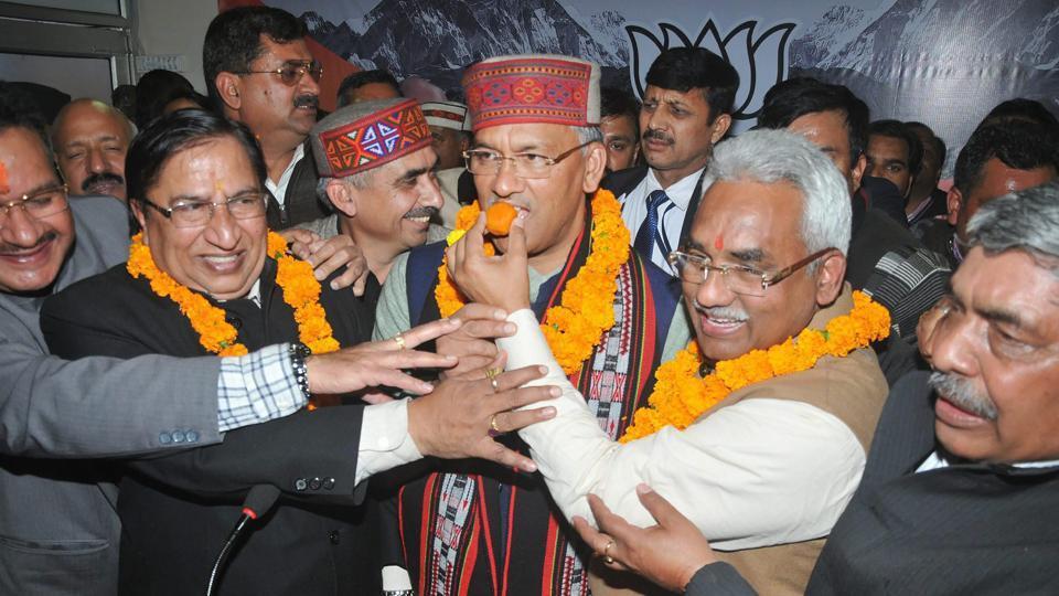 Bharatiya Janata Party supporters offer sweets to Uttarakhand chief minister Trivendra Singh Rawat in Dehradun.