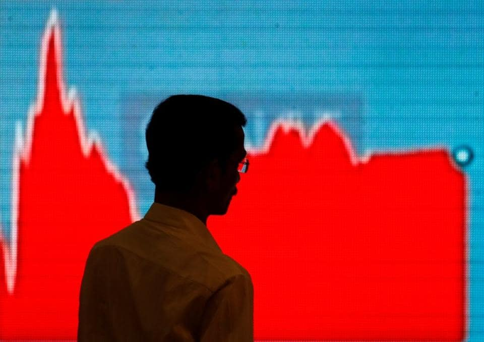 A man walks past a screen displaying news of markets update inside the Bombay Stock Exchange (BSE) building in Mumbai, India, February 6, 2018.