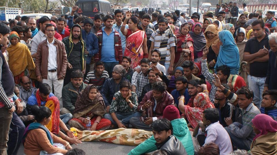 Family and locals block road and protest with the body of the boy who drowned in a water body in Jaipur on Monday.