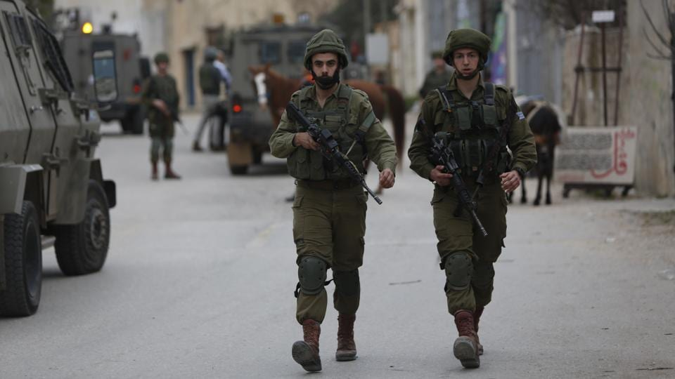Israeli soldiers search for a Palestinian attacker in Kifl Haris village near the Ariel settlement on February 5, 2018. A Palestinian stabbed an Israeli man to death at a bus stop near Ariel on Monday before fleeing the scene, police said.
