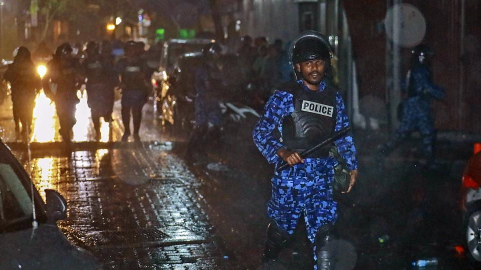 A Maldives policeman charges with baton towards protesters after the government declared a 15-day state of emergency in Male early Tuesday.