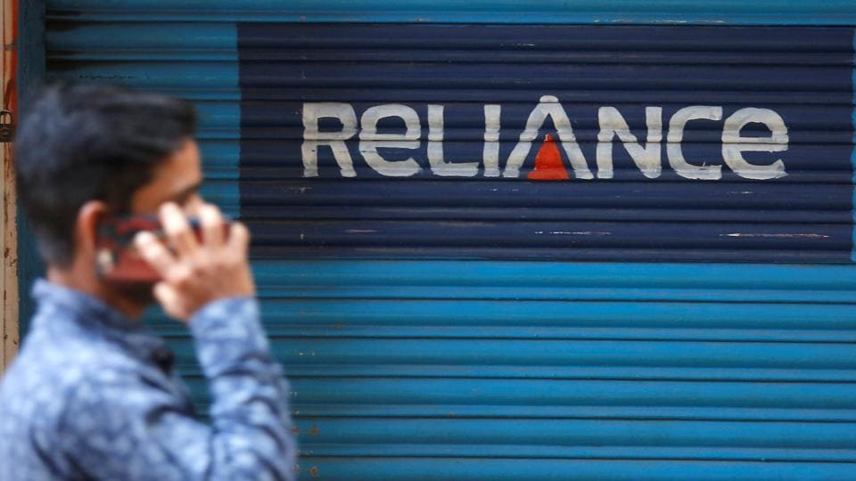 A man speaks on his mobile phone as he walks past a closed shop painted with an advertisement of Reliance Communications in Mumbai, India, January 29, 2018.