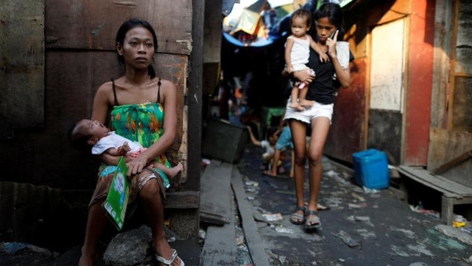 Residents outside shanties in Market 3, Manila. As night falls in the Philippine capital, few of the 700 families living in this portside shanty town venture out into the crime-ridden maze of sheet metal, crumbling cement and wooden boards -- a frontline of the bloody war on illegal drugs that has defined Rodrigo Duterte's presidency since it was unleashed in June 2016. (Dondi Tawatao / REUTERS)