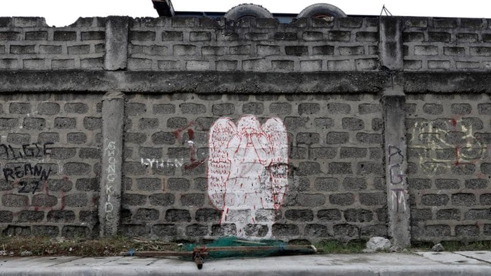 A crying angel is painted on a wall to mark a place where a woman was found dead after a police operation. The former drug user, who refused to give his name fearing reprisals, fled Market 3 like many of his friends who did the same, or are now dead. He even tried to take his own life. (Dondi Tawatao / REUTERS)