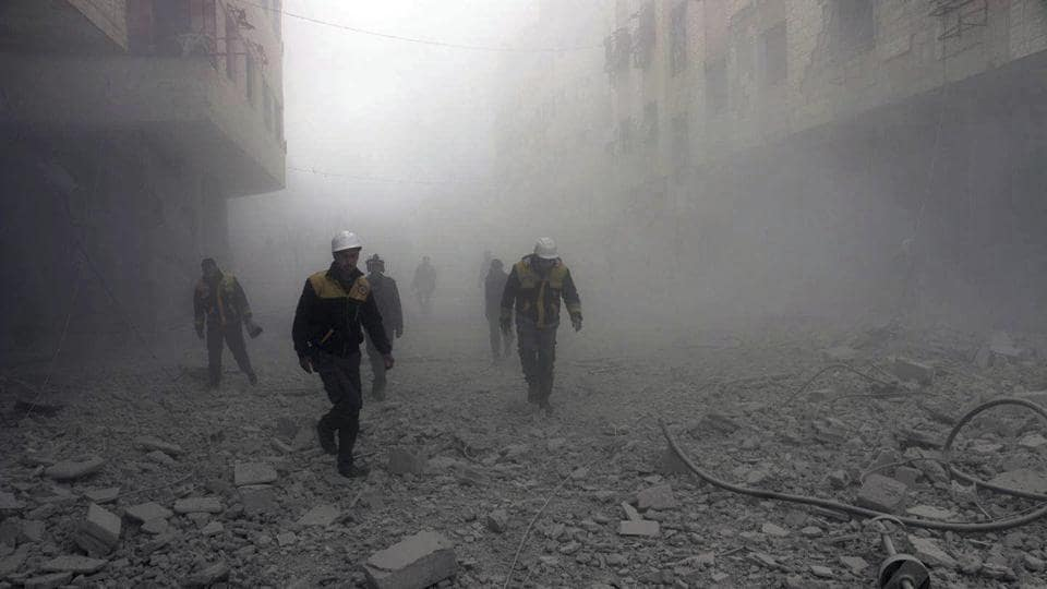 Photo provided by the Syrian Civil Defense group known as the White Helmets shows civil defense workers searching for survivors after airstrikes hit a rebel-held suburb near Damascus, Syria, on Monday.