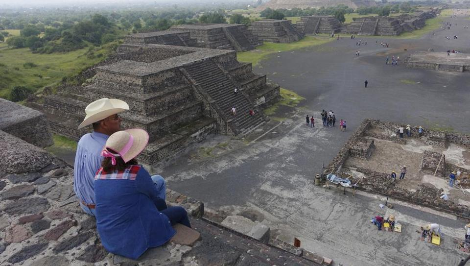 Tourists sit at the midway point of the Pyramid of The Moon viewing the ancient Pyramid of the Sun, back right, at the ruins of Teotihuacan in Teotihuacan, Mexico.