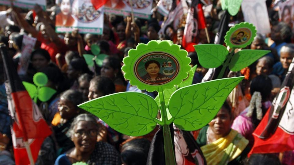 Supporters of AIADMK hold the party's 'two leaf' symbol at an election campaign rally.