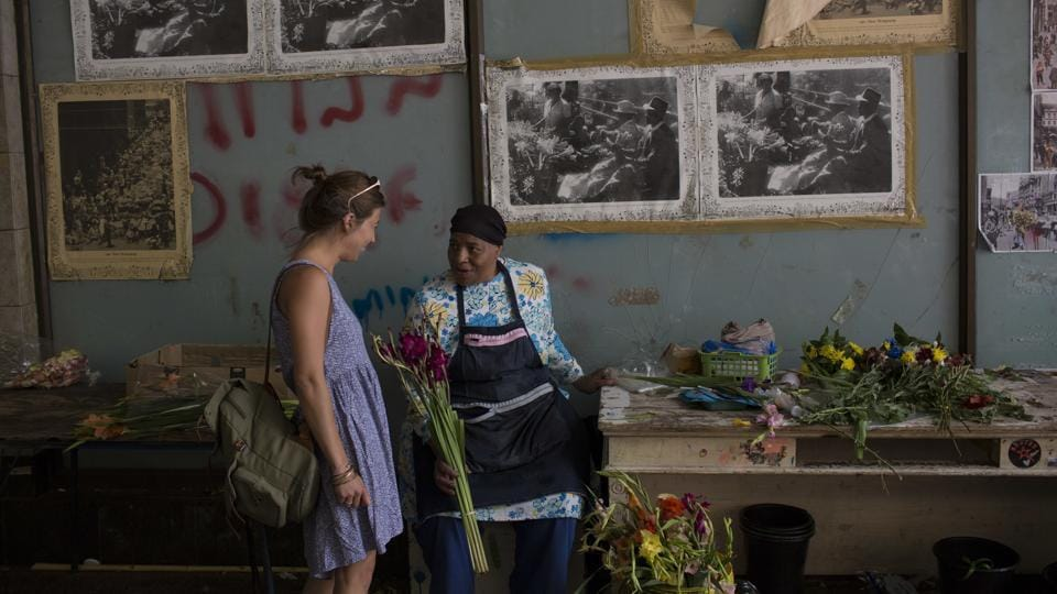 Faldela Dixon (R) talks to a customer at her flower shop in Cape Town. Dixon says customers don't buy as many flowers because of the drought, as they don't want to waste water on the flowers. From Cape Town's elegant suburbs to its gritty townships, people are working to reduce their water consumption across the board. (Bram Janssen / AP)