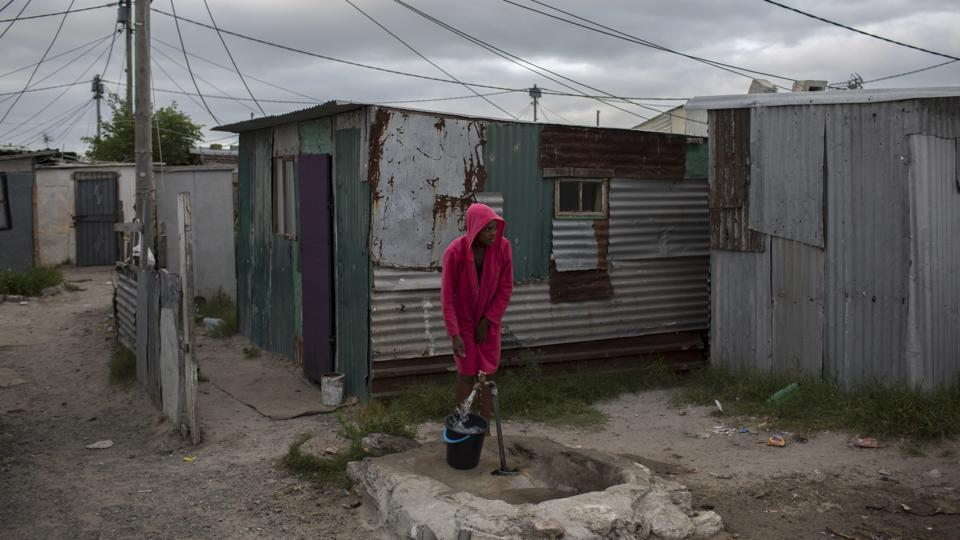 A woman collects water in a settlement near Cape Town. Some say poorer residents are unfairly blamed as concerns rise over wasting water. About a quarter of Cape Town's population lives in the informal settlements, where they get water from communal taps instead of individual taps at home like in the richer suburbs. (Bram Janssen / AP)