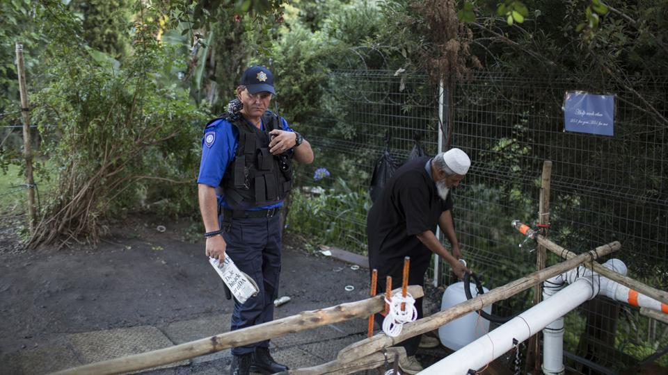 After an arrest over water sharing last week, police are guarding some natural springs to avoid any scuffles over access to the increasingly precious liquid. (Bram Janssen / AP)