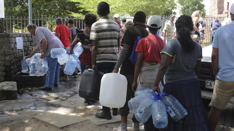 Residents queue for water at a natural spring. Some 70% of water used in Cape Town is consumed in homes, authorities say. Experts have said causes of the city's water shortages include climate change and huge population growth. (Bram Janssen / AP)