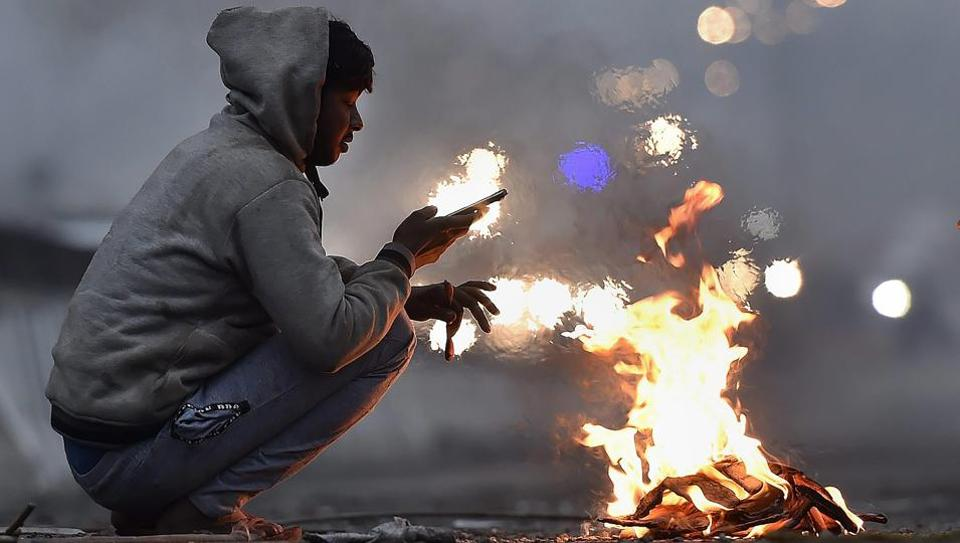 A man warms his hands around a bonfire on a cold winter morning in New Delhi.