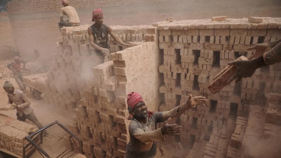 Factory workers stack bricks on a cart to take them to a warehouse in Dhaka, Bangladesh on February 6, 2018. (Mohammad Ponir Hossain / REUTERS)