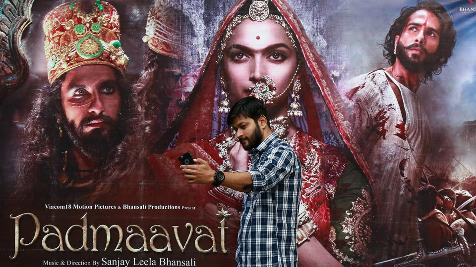 A cinemagoer takes a selfie in front of a poster of Bollywood movie Padmaavat outside a movie theatre in Kochi.