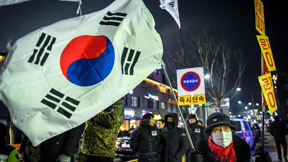 A woman holds the South Korean flag outside the stadium during the opening ceremony. (AFP)
