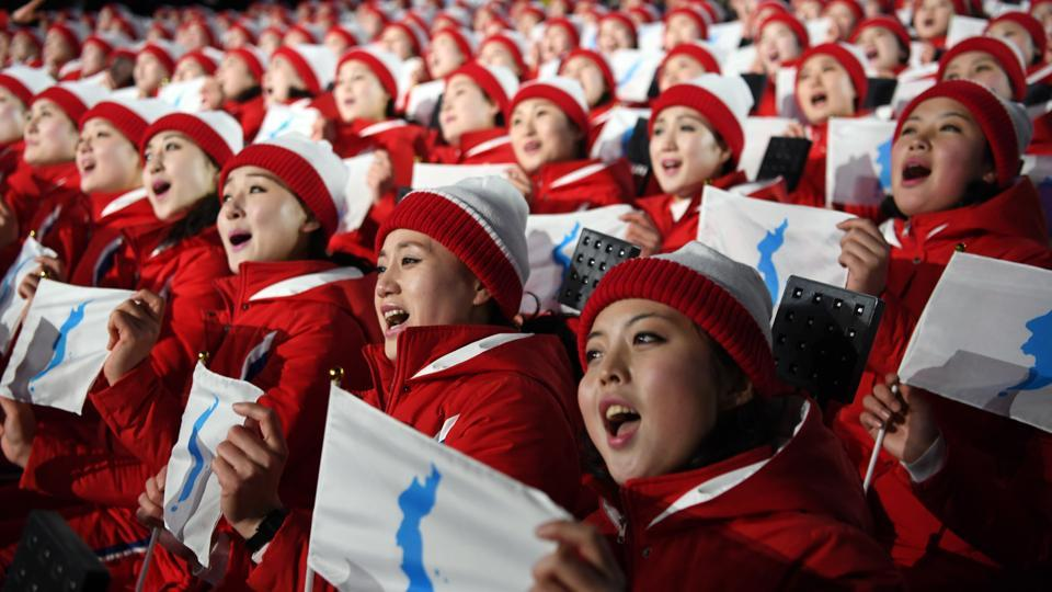 North Korean athletes sing and hold the unification flag depicting a unified Korean peninsula. (NYT)