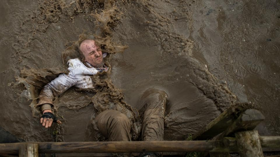 A competitor dressed in a white suit falls into muddy water as he negotiates an obstacle in the Tough Guy endurance event near Wolverhampton, England on February 4, 2018. (Oli Scarff / AFP)