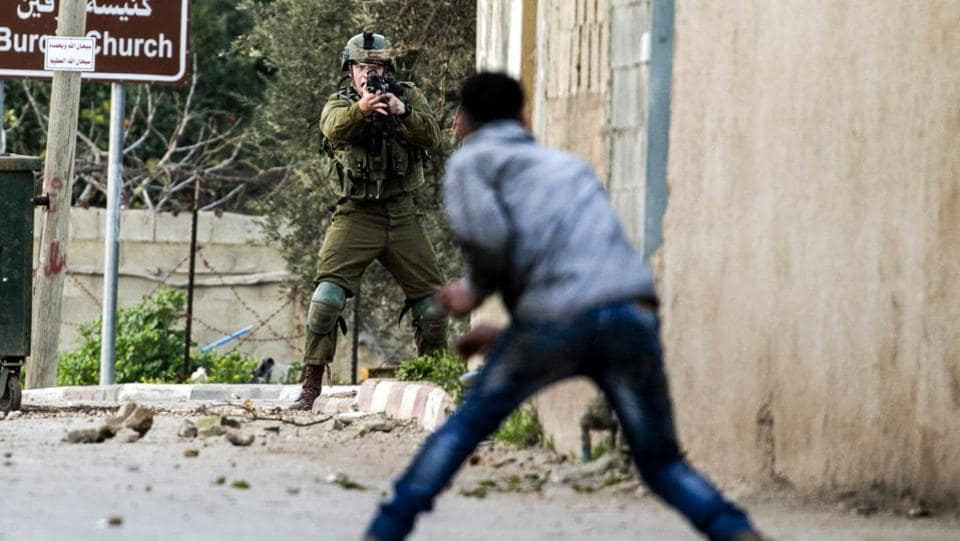 A Palestinian protester and an Israeli soldier face-off during an army search operation in the Palestinian village of Burqin in the northern occupied West Bank on February 3, 2018. (Jaafar Ashtiyeh / AFP)