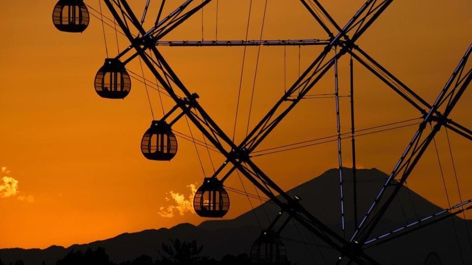 Japan's highest mountain Mt. Fuji is seen in the background over a ferris wheel during sunset at Kasai Rinkai Park in Tokyo on February 6, 2018. (Kazuhiro Nogi / AFP)