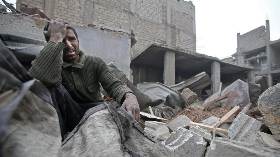 A Syrian man mourns over his destroyed home in the rebel-held besieged town of Arbin, in the eastern Ghouta region following airstrikes on the outskirts of Damascus on February 5, 2018. (Abdulmonam Eassa / AFP)