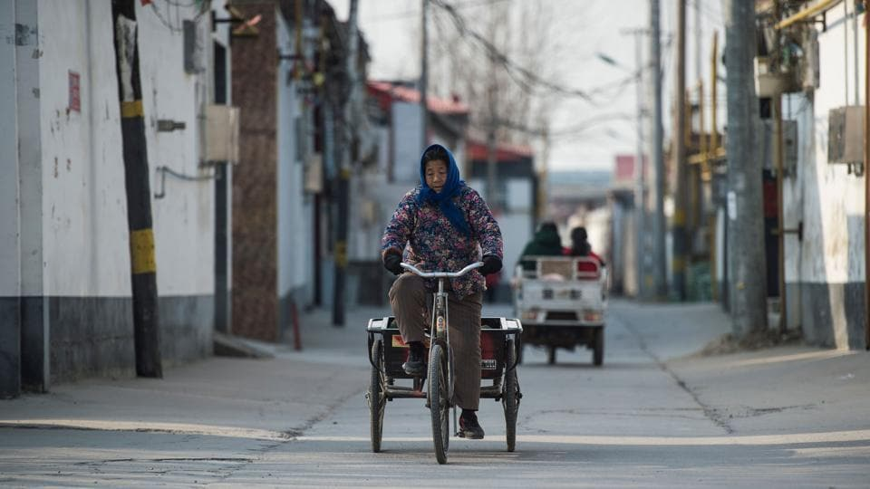A woman rides her bicycle in Niezhuang village, about 150 kilometres south of Beijing.  There were about 30.46 million rural people living below the national poverty line at the end of 2017.