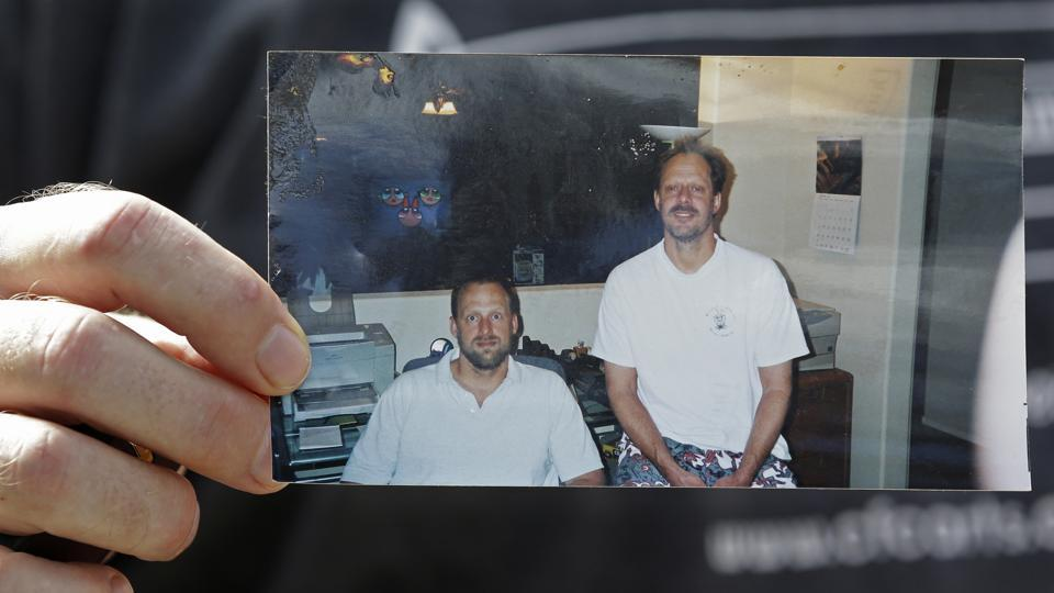 In this Oct. 2, 2017 file photo, Eric Paddock holds a photo of himself, at left, and his brother, Stephen Paddock, at right, outside his home in Orlando, Florida. An autopsy found Las Vegas shooter Stephen Paddock had anti-anxiety drugs in his system but was not under the influence of them and was otherwise healthy.