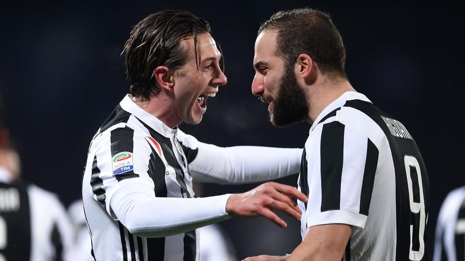 Juventus' forward Federico Bernardeschi (L) celebrates with teammate Gonzalo Higuain after scoring during their Italian Serie A match vs Fiorentina at the Atemio Franchi stadium in Florence on February 9, 2018.