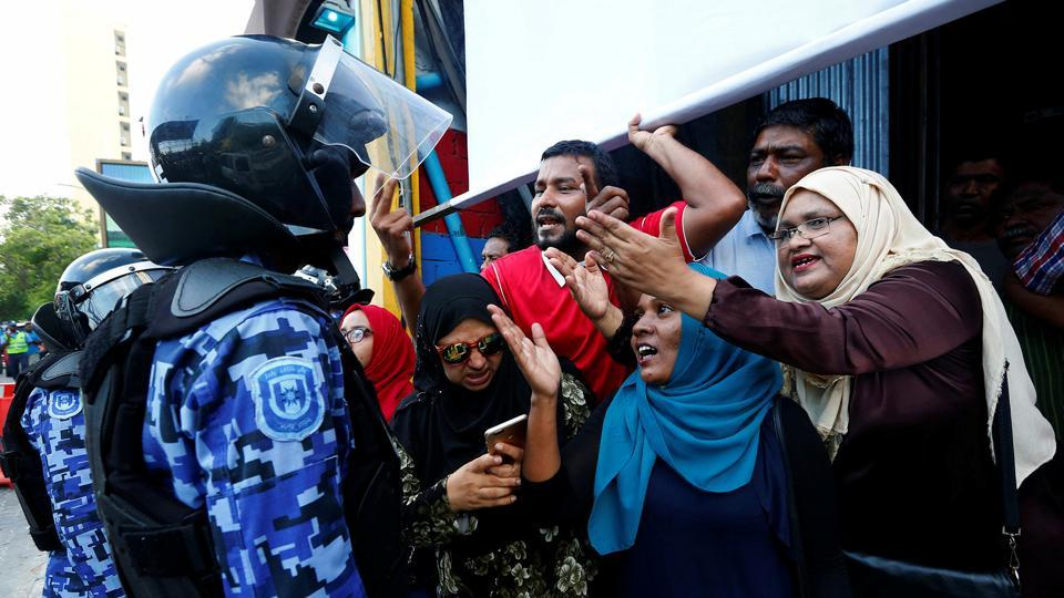 Maldivian opposition supporters argue with a police officer near the main opposition Maldives Democratic Party headquarters during a protest demanding the government to release jailed opposition leaders.