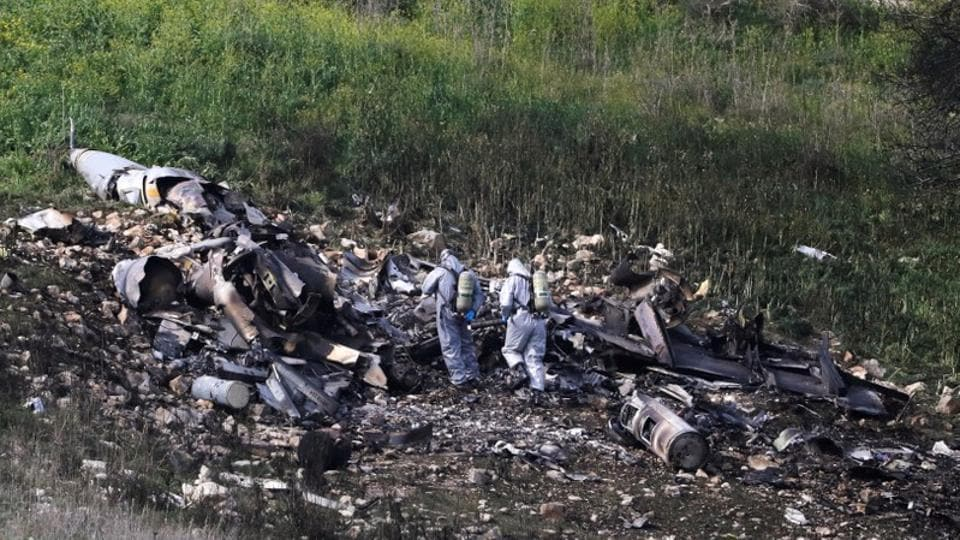 Israeli security forces examine the remains of an F-16 Israeli war plane near the Israeli village of Harduf Israel