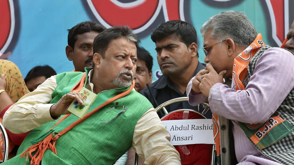 West Bengal BJP president Dilip Ghosh speaks with party leader Mukul Roy at a convention in Kolkata. Mukul Roy was a former Trinamool leader who joined BJP.