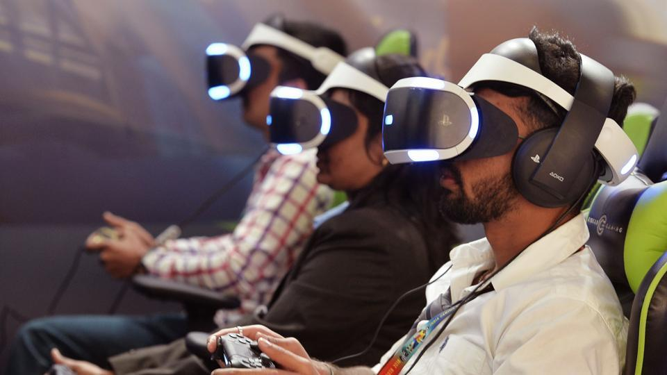 Gamers wearing virtual reality (VR) glasses play games at a stall during the India Gaming Show South 2018 expo at the Bangalore International Exhibition Centre on January 19, 2018.