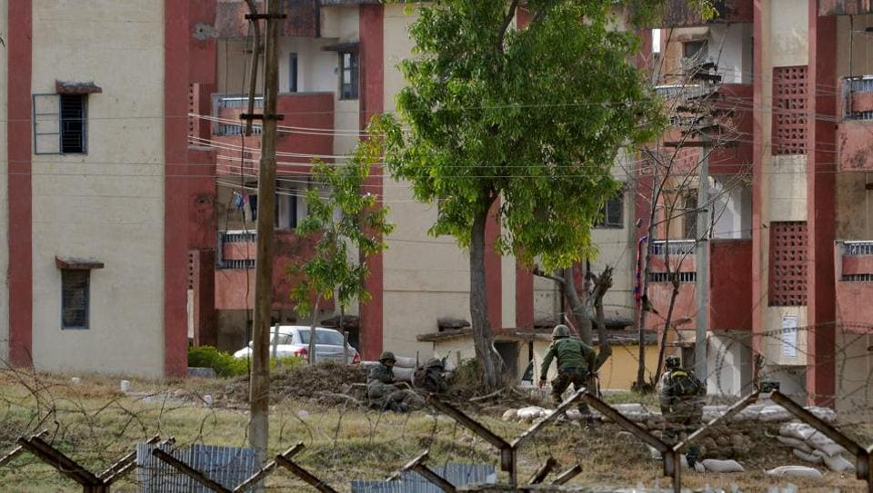 Army soldiers take position as they surround the residential quarters where militants are believed to be holed up in an Army camp in Jammu, on Sunday.