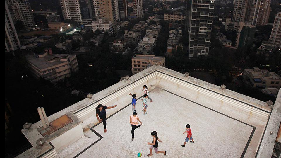 One has to watch how hard one kicks the ball, when there's a chance it could plummet several storeys. But the terrace and building lobby are often the only places available for play in overcrowded Mumbai. (Hemanshi Kamani / HT Photo)