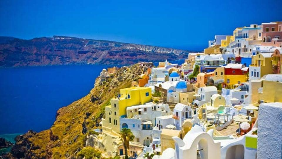 Santorini in Greece is known for its electric blue skies, white-coloured houses, and the dark blue ocean.