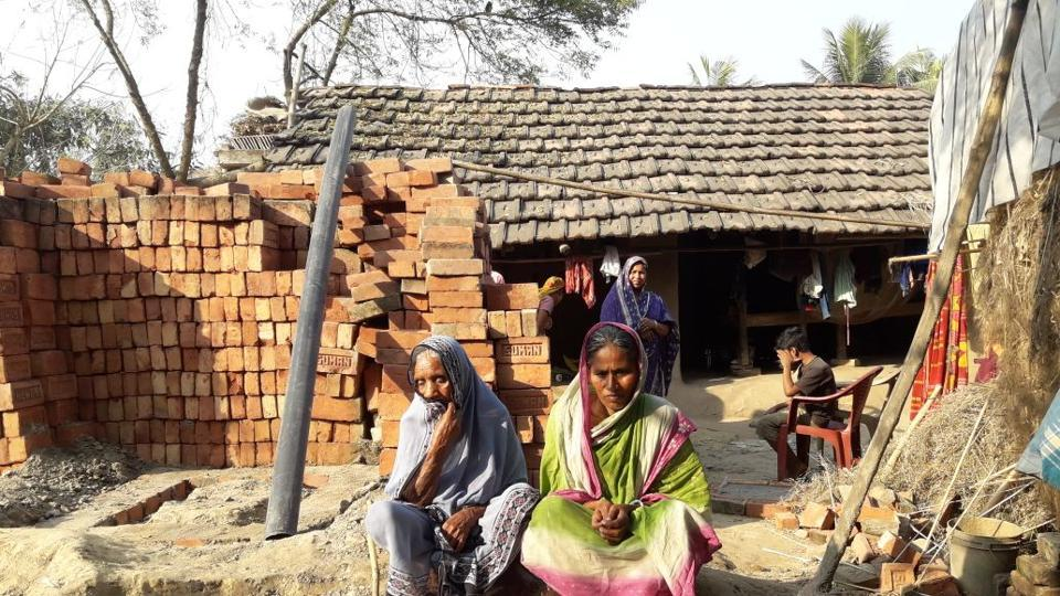 Rahima Bewa (left) and daughter, Kamala Bewa, sit in front of bricks bought to build a toilet at their home in  Nowdapara in West Bengal's Murshidabad district.