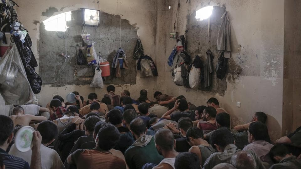 Suspected Islamic State members sit inside a small room in a prison south of Mosul.