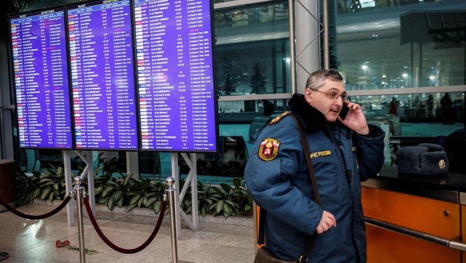 A Russian emergency employee stands next to flowers placed in tribute to the plane crash victims under of the flight schedule timetables at the Domodedovo International Airport. President Vladimir Putin has ordered a special commission to investigate the crash. (Maxim Zmeyev / AFP)