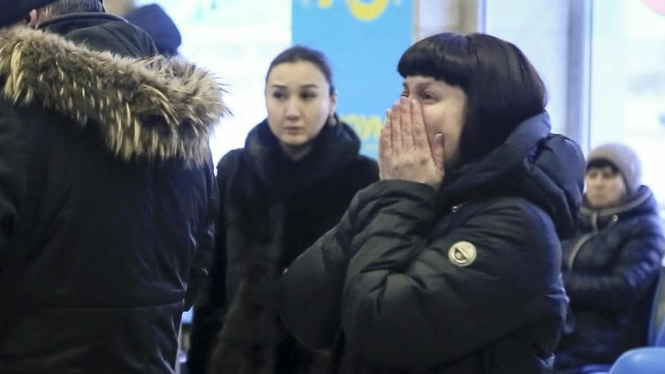 Relatives and friends of those on the Saratov Airlines An-148 flight react while gathering at an airport outside Orsk, Russia on Sunday. A Swiss citizen and a citizen of Azerbaijan were among the fatalities on a list released by the emergency services ministry. Three children also died including a five-year-old girl. (Orsk.ru via / AP)
