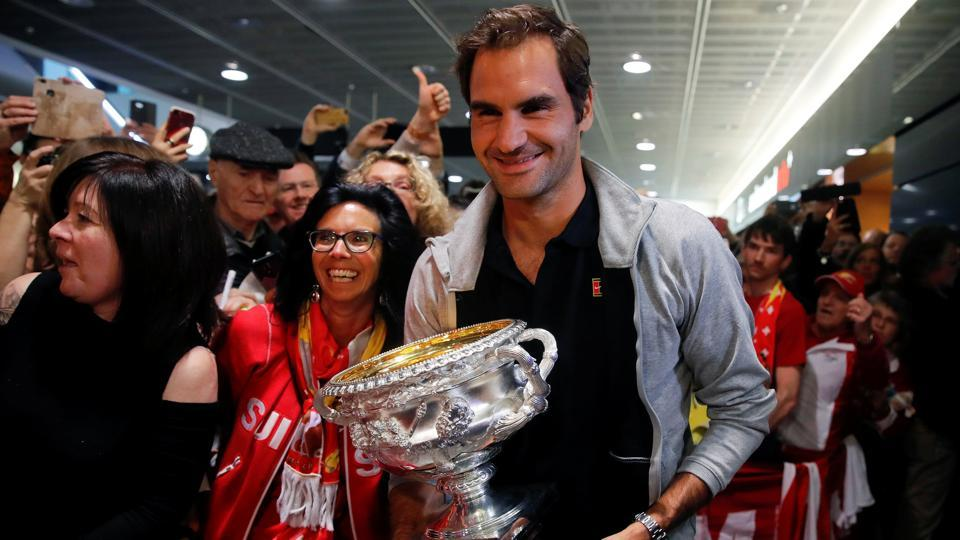 Switzerland's Roger Federer holds his Australian Open trophy as he is welcomed by fans in Zurich.